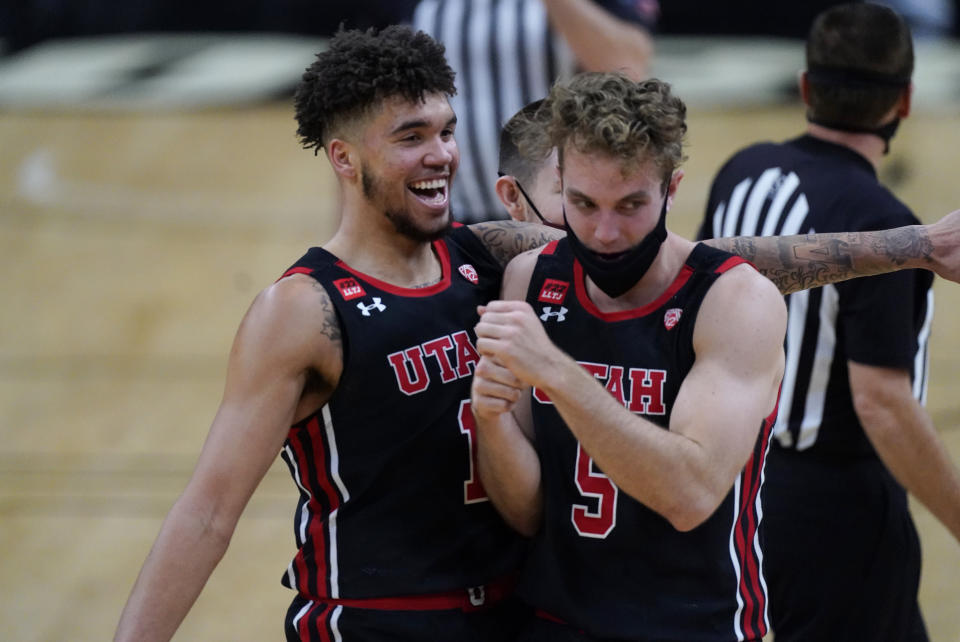 Utah forward Timmy Allen, left, jokes with guard Jaxon Brenchley in the second half of an NCAA college basketball game against Colorado, Saturday, Jan. 30, 2021, in Boulder, Colo. Utah won 77-74. (AP Photo/David Zalubowski)