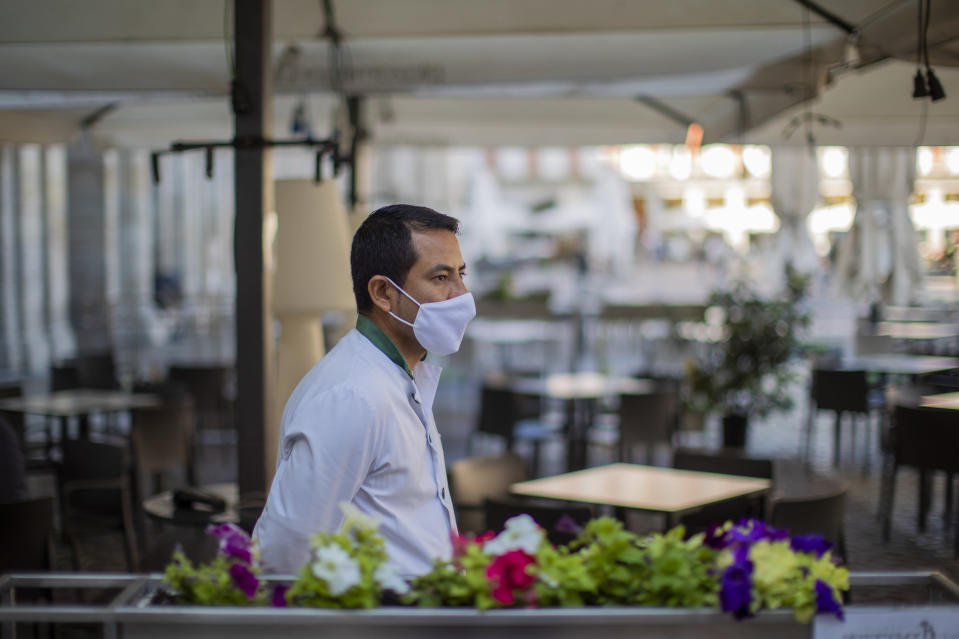 A waiter wearing a face mask to prevent the spread of coronavirus waits for customers in downtown Madrid, Spain, Friday, Oct. 9, 2020. Spanish Prime Minister Pedro Sánchez is holding a Cabinet meeting to consider declaring a state of emergency for Madrid in order to impose stronger anti-virus restrictions on reluctant regional authorities. (AP Photo/Manu Fernandez)