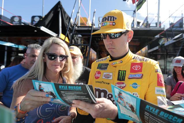 Kyle Busch signs autographs as he enters the garage for a NASCAR Cup Series auto race practice at Homestead-Miami Speedway in Homestead, Fla., Saturday, Nov. 16, 2019. (AP Photo/Luis M. Alvarez)