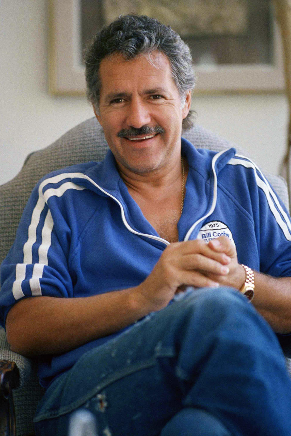 """FILE - Alex Trebek poses in his home in Los Angeles, in this July 7, 1988, file photo. Jeopardy!"""" host Alex Trebek died Sunday, Nov. 8, 2020, after battling pancreatic cancer for nearly two years. Trebek died at home with family and friends surrounding him, """"Jeopardy!"""" studio Sony said in a statement. Trebek presided over the beloved quiz show for more than 30 years.(AP Photo/Alan Greth, File)"""