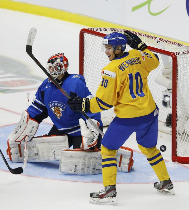 Sweden's Alexander Wennberg (R) celebrates a goal by teammate Lucas Wallmark, not seen, on Finland's goalie Juuse Saros during the second period of their IIHF World Junior Championship gold medal ice hockey game in Malmo, Sweden, January 5, 2014. REUTERS/Alexander Demianchuk (SWEDEN - Tags: SPORT ICE HOCKEY)