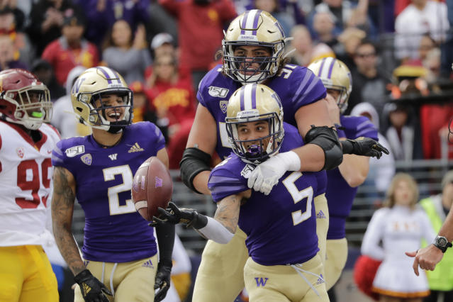 Washington's Andre Baccellia (5) celebrates his recovery of a fumble in the end zone for a touchdown with Jaxson Kirkland (51) and Aaron Fuller (2) against Southern Cal in the first half of an NCAA college football game Saturday, Sept. 28, 2019, in Seattle. (AP Photo/Elaine Thompson)