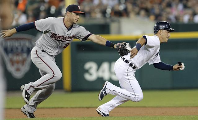Minnesota Twins third baseman Trevor Plouffe, left, tags out Detroit Tigers' Jose Iglesias to complete a double play on a Torii Hunter line drive that was caught in the fifth inning of a baseball game in Detroit, Wednesday, Aug. 21, 2013. (AP Photo/Paul Sancya)