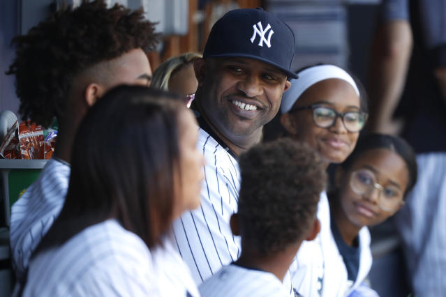 New York Yankees' CC Sabathia, with his family, sits in the dugout before being honored before a baseball game against the Toronto Blue Jays, Sunday, Sept. 22, 2019, in New York. (AP Photo/Michael Owens)