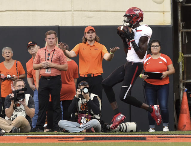 An Oklahoma State fan reacts to Texas Tech wide receiver T.J. Vasher catching a pass in the end zone for a touchdown during the first half of an NCAA college football game in Stillwater, Okla., Saturday, Sept. 22, 2018. (AP Photo/Brody Schmidt)