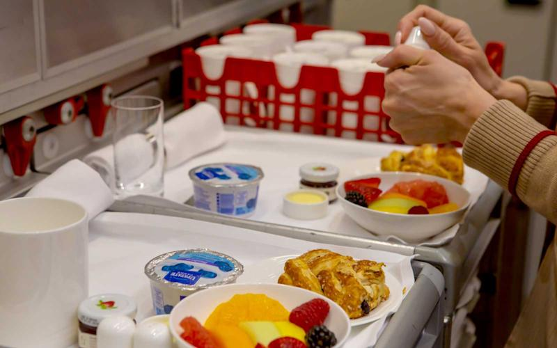 Cabin crew plate trays to take out to passengers. | Talia Avakian