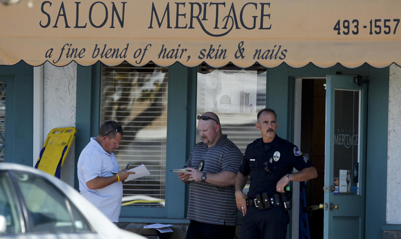 Investigators stand near the site where six people were killed and three were wounded in a shooting at a hair salon in Seal Beach, Calif., Wednesday, Oct. 12, 2011. The six deaths were confirmed and the other three victims were taken to a hospital in critical condition, police Sgt. Steve Bowles told The Associated Press. (AP Photo/Chris Carlson)