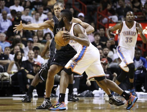 Miami Heat's Shane Battier (31) tries to block Oklahoma City Thunder's James Harden (13) during the first half of an NBA basketball game in Miami, Wednesday, April 4, 2012. (AP Photo/J Pat Carter)