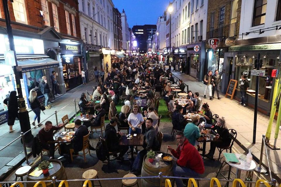 People eating on restaurant tables placed outside on Old Compton St in Soho, in 2020   (Yui Mok/PA Wire)