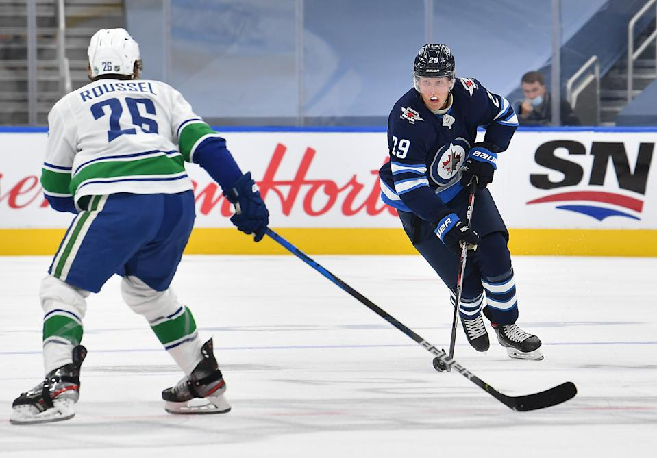 EDMONTON, ALBERTA - JULY 29: Patrik Laine #29 of the Winnipeg Jets skates the puck through the neutral zone against Antoine Roussel #26 of the Vancouver Canucks during the first period of an exhibition game prior to the 2020 NHL Stanley Cup Playoffs at Rogers Place on July 29, 2020 in Edmonton, Alberta. (Photo by Andy Devlin/NHLI via Getty Images)