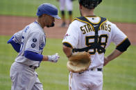 Los Angeles Dodgers' Mookie Betts, left, crosses home plate past Pittsburgh Pirates catcher Jacob Stallings after hitting a solo home run during the first inning of a baseball game in Pittsburgh, Thursday, June 10, 2021. (AP Photo/Gene J. Puskar)