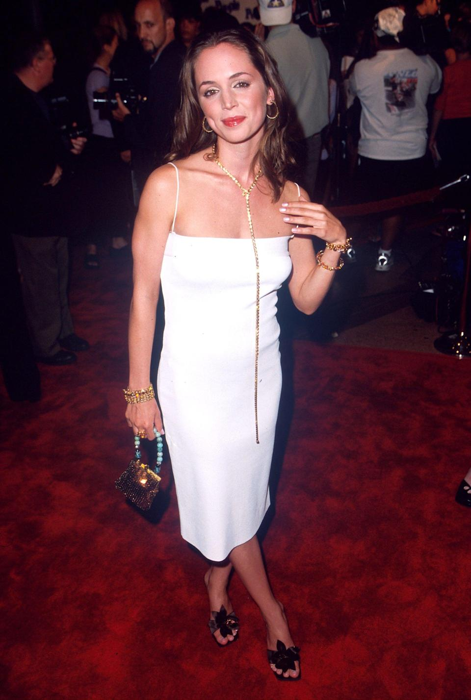 """<p>Eliza played Missy, who had a tough, edgy style in the film. But Eliza surprised in an elegant white slip sheath - a very <a class=""""link rapid-noclick-resp"""" href=""""https://www.popsugar.com/Kate-Moss"""" rel=""""nofollow noopener"""" target=""""_blank"""" data-ylk=""""slk:Kate Moss"""">Kate Moss</a> '90s reference - that she then jazzed up with accessories that spoke to the decade. Eliza carried a mini crystal-studded purse with a turquoise beaded handle, wore brown satin heels with a flower adornment, and finished the outfit with a matching gold hoop and drop necklace set. Bangles were the finishing touch.</p>"""