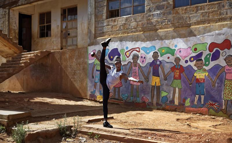 In this photo taken Friday, Dec. 9, 2016, Kenyan ballet dancer Joel Kioko, 16, strikes a pose as a joke as he walks through the courtyard of a school where he was teaching young dancers, in the Kibera slum of Nairobi, Kenya. In a country not usually associated with classical ballet, Kenya's most promising young ballet dancer Joel Kioko has come home for Christmas from his training in the United States, to dance a solo in The Nutcracker and teach holiday classes to aspiring dancers in Kibera, the Kenyan capital's largest slum. (AP Photo/Ben Curtis)