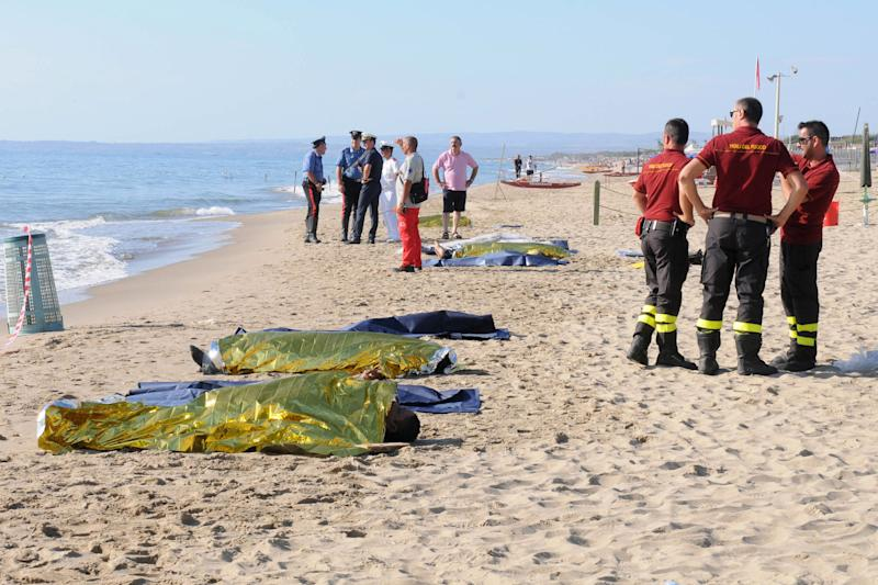 Firefighters and police officers stand next to the lifeless bodies of six migrants who, according to Italian coast guard officials, drowned after their boat ran aground on a sandbar and they tried to swim to shore, near Catania, southern Italy, Saturday, Aug. 10, 2013. The boat, with some 100 migrants aboard, became stranded early Saturday 15 meters (50 feet) off a beach popular with tourists and locals. (AP Photo/Carmelo Imbesi)