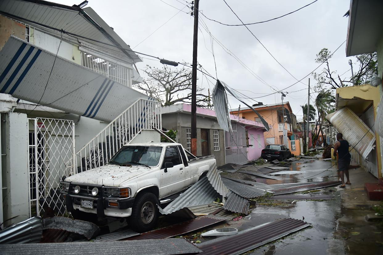Residents of San Juan, Puerto Rico, deal with damage to their homes on Sept. 20, 2017, as Hurricane Maria batters the island.