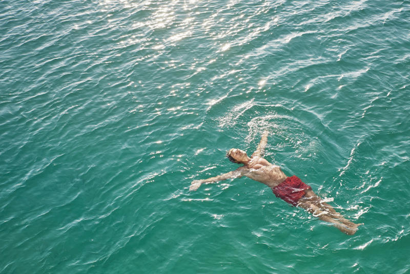 Mature man floating in emerald water