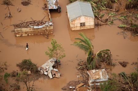 People walk through floodwater near Beira, Mozambique, in the aftermath of Cyclone Idai, March 23, 2019. REUTERS/Mike Hutchings