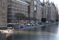Three men in a boat hacked away at ice to create a watery perimeter around the Dutch prime minister's office in The Hague, Netherlands, Thursday, Feb. 11, 2021. With ice likely thick enough in coming days for people to skate on the Hofvijver lake that fringes one side of the Dutch parliamentary complex, workers made sure the skaters couldn't get right up to Prime Minister Mark Rutte's office by bashing through ice. (AP Photo/Mike Corder)