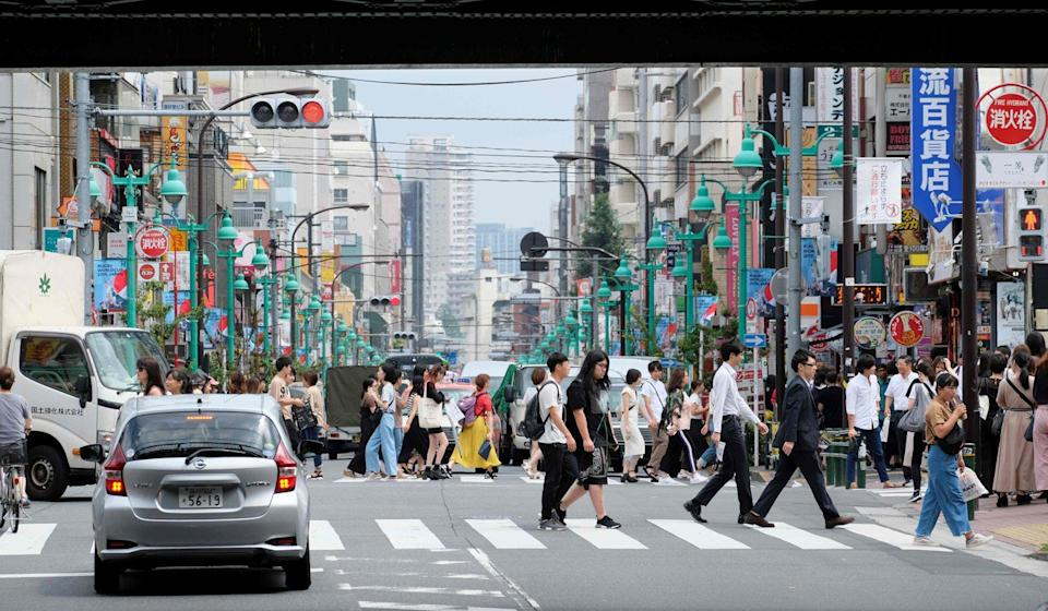 People cross a street in Shin-Okubo district in Tokyo. Photo: AFP