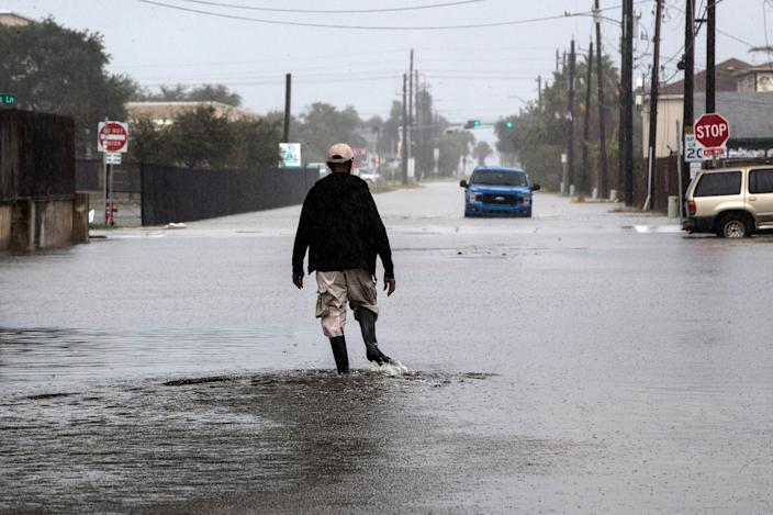 A man walks through a street flooded by Tropical Storm Beta on Monday, Sept. 21, 2020, in Galveston, Texas.