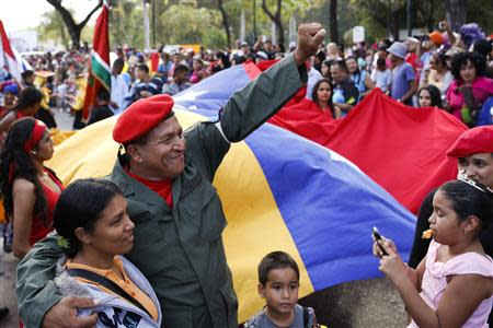 Man dressed as late Venezuelan President Hugo Chavez waves during the Carnival festival in Caracas