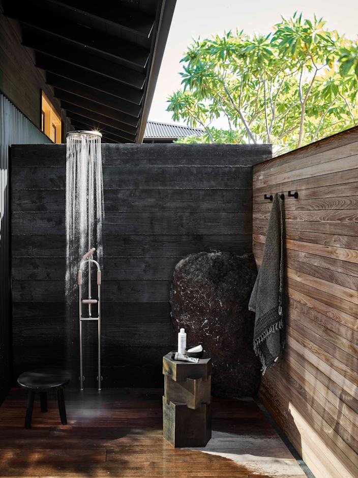 There are no indoor showers at Hale Huna. Open-air stalls echo the materiality (ipe and concrete) and intent (unity with nature) of the other outdoor rooms. A ceramic taboret by Bari Ziperstein is an angular counterpoint to the organic sculptural quality of the corner lava rock. Rain shower by Calazzo, black resin stool by San Francisco artist Tina Frey.