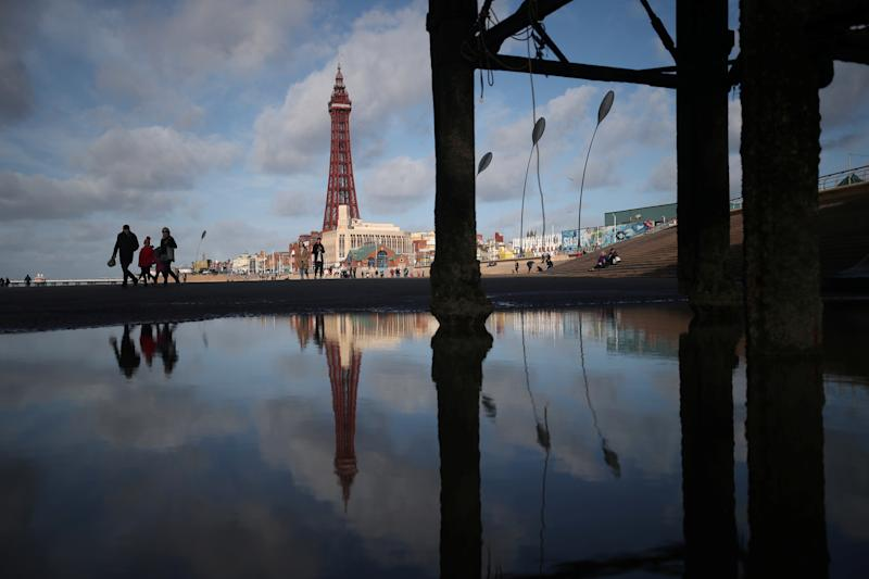 People walk along the beach as the Blackpool Tower is reflected in a pool under the pier, in Blackpool, Britain, October 22, 2018. REUTERS/Hannah McKay