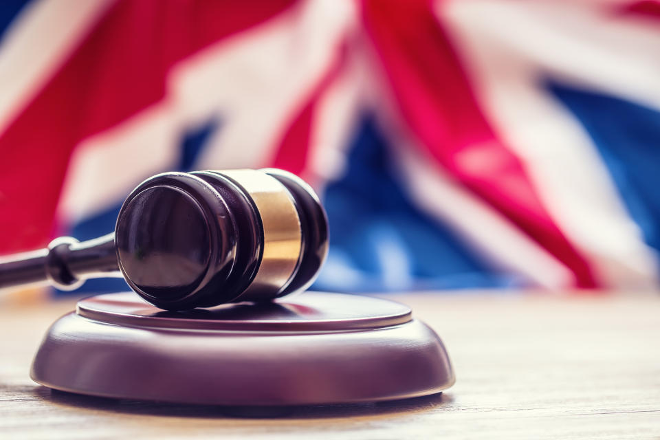 Judges wooden gavel with UK flag in the background. Symbol for jurisdiction.