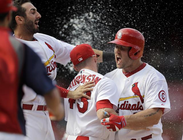 St. Louis Cardinals' Matt Holliday, right, is congratulated by teammates including Shane Robinson, center, and Matt Carpenter, left, after hitting a walk-off single to defeat the Pittsburgh Pirates 6-5 in a baseball game, Thursday, Aug. 15, 2013, in St. Louis. (AP Photo/Jeff Roberson)