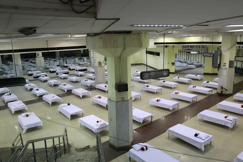 Housekeeping staff members prepare beds in a temporary quarantine facility for the incoming passengers inside a closed terminal building, at the Netaji Subhas Chandra Bose International Airport (CCU), after the government allowed domestic flight services to resume, during the government extended nationwide lockdown to slow the spread of the coronavirus disease (COVID-19), in Kolkata, India, May 28,2020. (Photo by Debajyoti Chakraborty/NurPhoto via Getty Images)