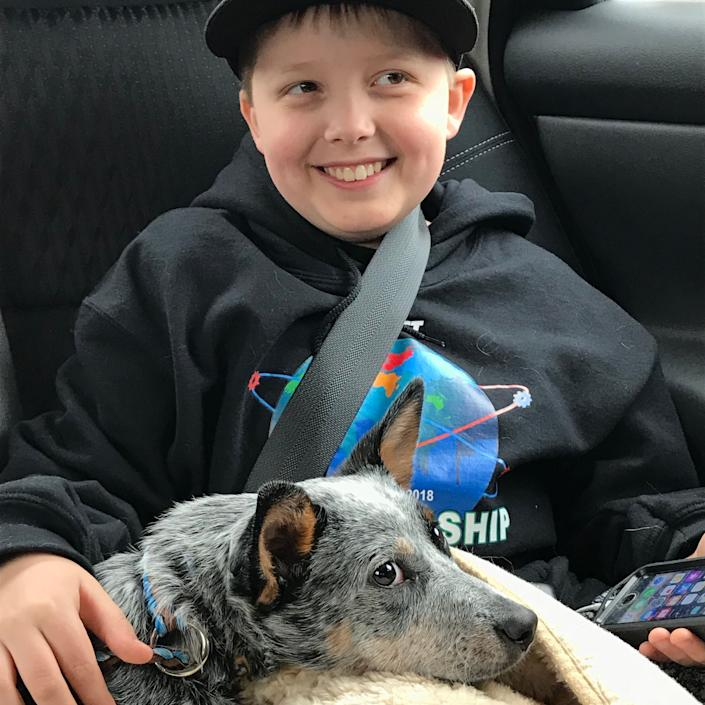 """""""This is Terabyte (Tera for short) and our youngest son. Tera is a cattle dog, found dumped in a field. She&rsquo;s super smart, sweet, snuggly, and also happens to be deaf. I took this photo right after we had signed the adoption papers and picked her up from her foster family."""" -- <i><a href=""""https://www.instagram.com/kristinchristopherjewelry/"""" rel=""""nofollow noopener"""" target=""""_blank"""" data-ylk=""""slk:Kristin Cooper"""" class=""""link rapid-noclick-resp"""">Kristin Cooper</a>, Tera's mom</i>"""