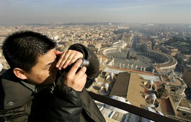 A tourist takes a photograph from the balcony overlooking Saint Peter's square at the Vatican January 18, 2005.