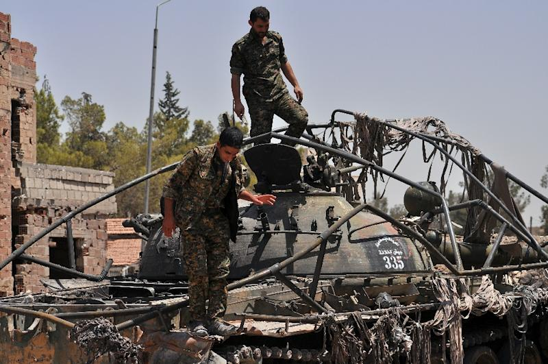 Kurdish People's Protection Units fighters stand on top of a tank bearing Islamic State militant logos in the Al-Nashwa neighbourhood in the northeastern Syrian province of Hasakeh on July 26, 2015 (AFP Photo/Delil Souleiman)