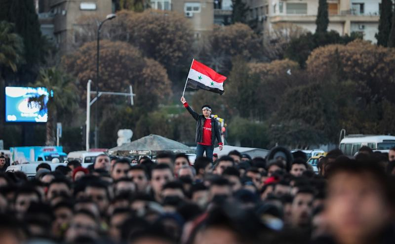 A Syrian football fan waves the national flag while watching his team play Australia in the Asian Cup on a big screen in Damascus on January 15, 2019 (AFP Photo/LOUAI BESHARA)