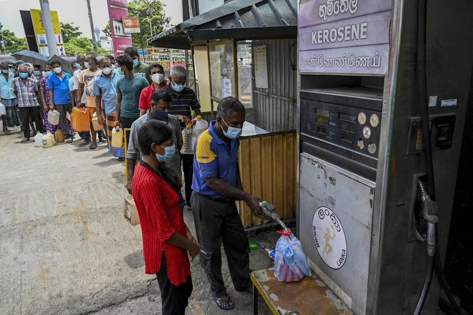 People stand in a queue to buy kerosene oil used in cooking stoves in Colombo following Sri Lanka's declaration of a state of emergency (AFP via Getty Images)