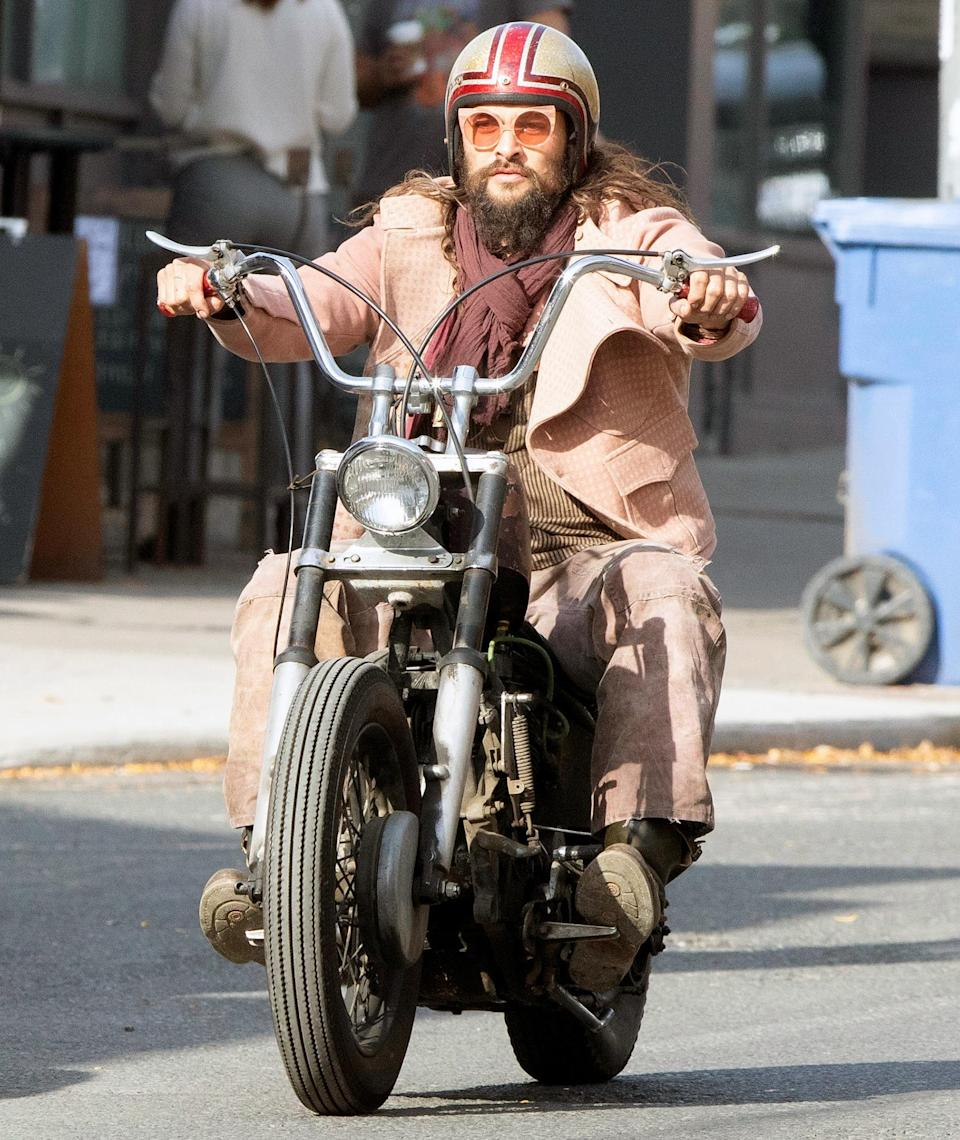 <p>Jason Momoa wears a pink jacket and sunglasses as he takes his motorcycle for a spin in Toronto, Canada on Sunday. </p>