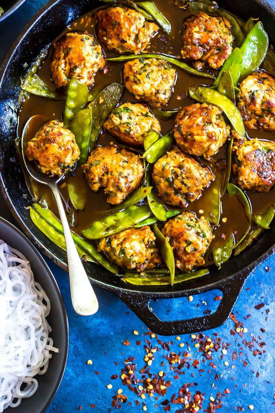 """<p>This bowl of Shirataki noodles with snap peas and meatballs by<a href=""""https://www.castironketo.net/blog/keto-asian-bbq-meatball-noodle-bowl"""" rel=""""nofollow noopener"""" target=""""_blank"""" data-ylk=""""slk:Cast Iron Keto"""" class=""""link rapid-noclick-resp""""> Cast Iron Keto</a> takes only 30 minutes to whip up and uses savory ingredients and spices like garlic, red pepper, sriracha, and tamari to give the dish a huge burst of flavor. Each serving is under 400 calories and has roughly 24 grams of protein to prevent mindless snacking later on.</p>"""