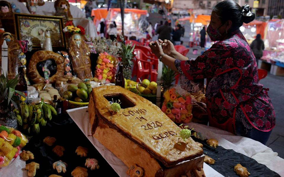 Lourdes Vasquez arranges a coffin-shaped bread and other offerings at an altar set up in honour of the victims of the coronavirus disease at a market before Day of the Dead celebrations, in La Paz, Bolivia -  DAVID MERCADO / REUTERS