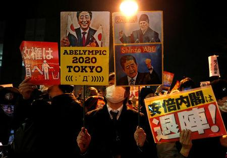 Protesters shout slogans and hold placards during a rally denouncing Japanese Prime Minister Shinzo Abe and Finance Minister Taro Aso over a suspected cover-up of a cronyism scandal in front of Abe's official residence in Tokyo, Japan March 14, 2018. REUTERS/Issei Kato