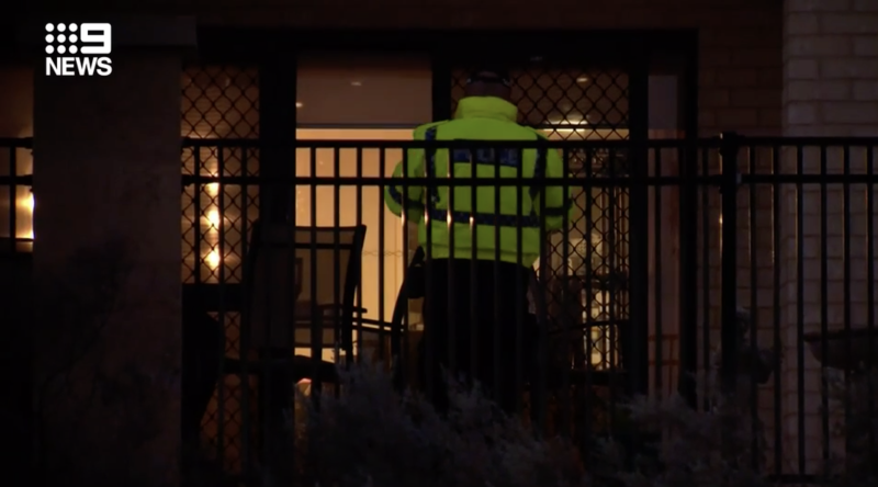 A police officer looks through a home in Waikiki, Perth.