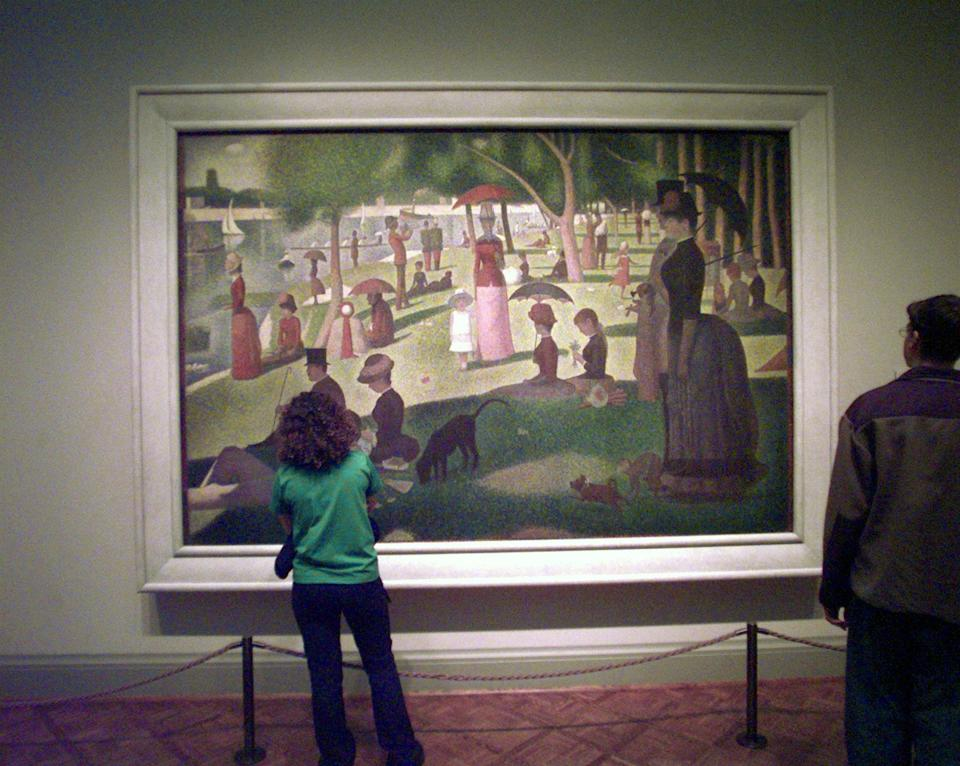 """A patron takes in """"A Sunday on La Grande Jatte-1884"""" by French Post Impressionist artist Georges Seurat at the Art Institute of Chicago, Oct. 30, 1998. The museum received two conti-crayon drawings by Seurat that were done as a figure study for his famous painting. The drawings came from the Museum of Modern Art in New York which had to give away four impressionist artworks valued at more than $40 million because the patron who bequeathed them at her death in 1948 believed they would no longer be """"modern"""" after 50 years.  (AP Photo/Charles Bennett)"""