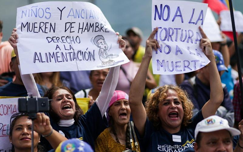 A Venezuelan opposition supporter holds up a a sign saying that children and old people are dying of hunger - AFP