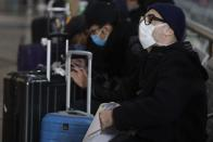 People wearing sanitary masks sit as they wait at the Centrale main railway station in Milan, Italy, Monday, Feb. 24, 2020. Italy has been scrambling to check the spread of Europe's first major outbreak of the new viral disease amid rapidly rising numbers of infections and a third death, calling off the popular Venice Carnival, scrapping major league soccer matches in the stricken area and shuttering theaters, including Milan's legendary La Scala. (AP Photo/Luca Bruno)