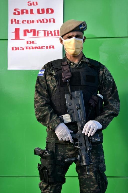 """A Honduran presidential guard soldier wears a face mask and gloves as he stands next to a sign reading """"For your health, 1 meter distance"""" outside a supermarket in Tegucigalpa, on March 19, 2020"""
