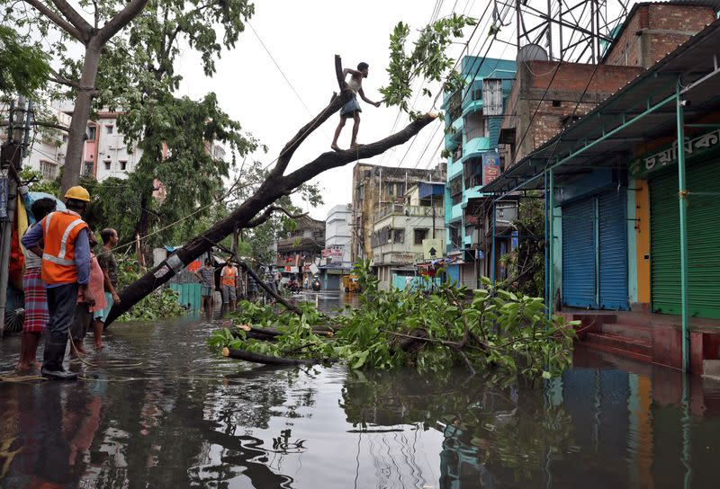 A man cuts branches of an uprooted tree after Cyclone Amphan made its landfall, in Kolkata
