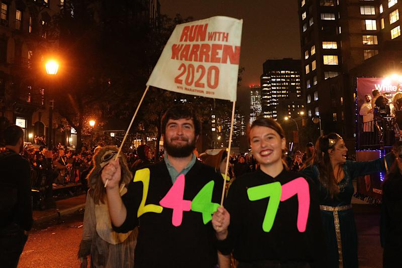 Revelers carrying political sign in support of Elizabeth Warren march during the 46th annual Village Halloween Parade in New York City. (Gordon Donovan/Yahoo News)