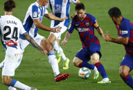 Barcelona's Lionel Messi fights for the ball next to Luis Suarez, against Espanyol's Marc Roca, Fernando Calero and Bernardo Espinosa, left, during the Spanish La Liga soccer match between FC Barcelona and RCD Espanyol at the Camp Nou stadium in Barcelona, Spain, Wednesday, July 8, 2020. (AP Photo/Joan Monfort)