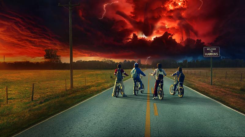Promotional art from Netflix original series Stranger Things showing four children on bicycles looking at a black and red sky