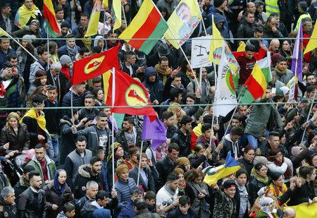 People hold placards during a demonstration organised by Kurds, in Frankfurt.