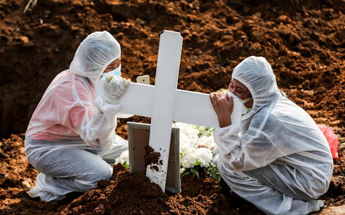Relatives clad in hazmat suits mourn at the grave of a Covid-19 victim in Medan, Indonesia on 13 August 2021 - Dedi Sinuhaji/Shutterstock